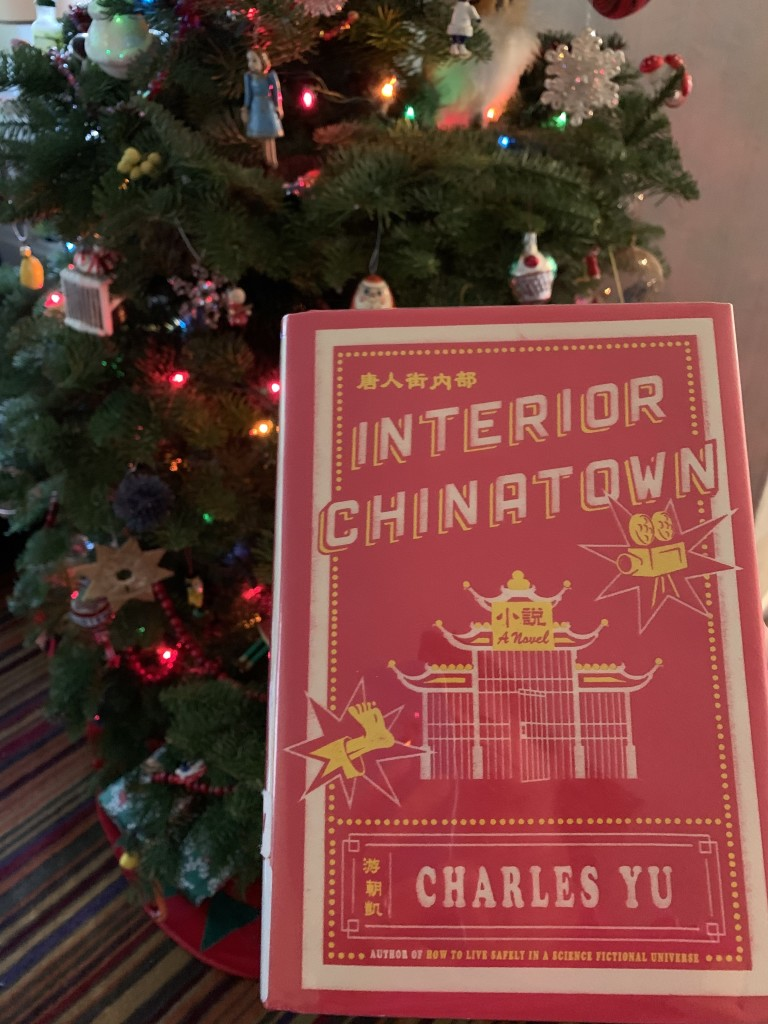 "Charles Yu's novel ""Interior Chinatown"" in front of Christmas tree"